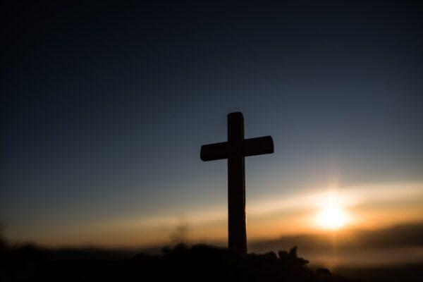 Silhouette of catholic cross and sunrise