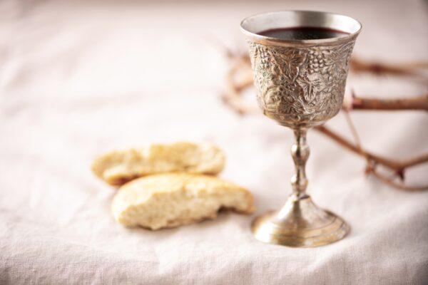 Unleavened bread, chalice of wine, silver kiddush wine cup on canva background. Communion still life